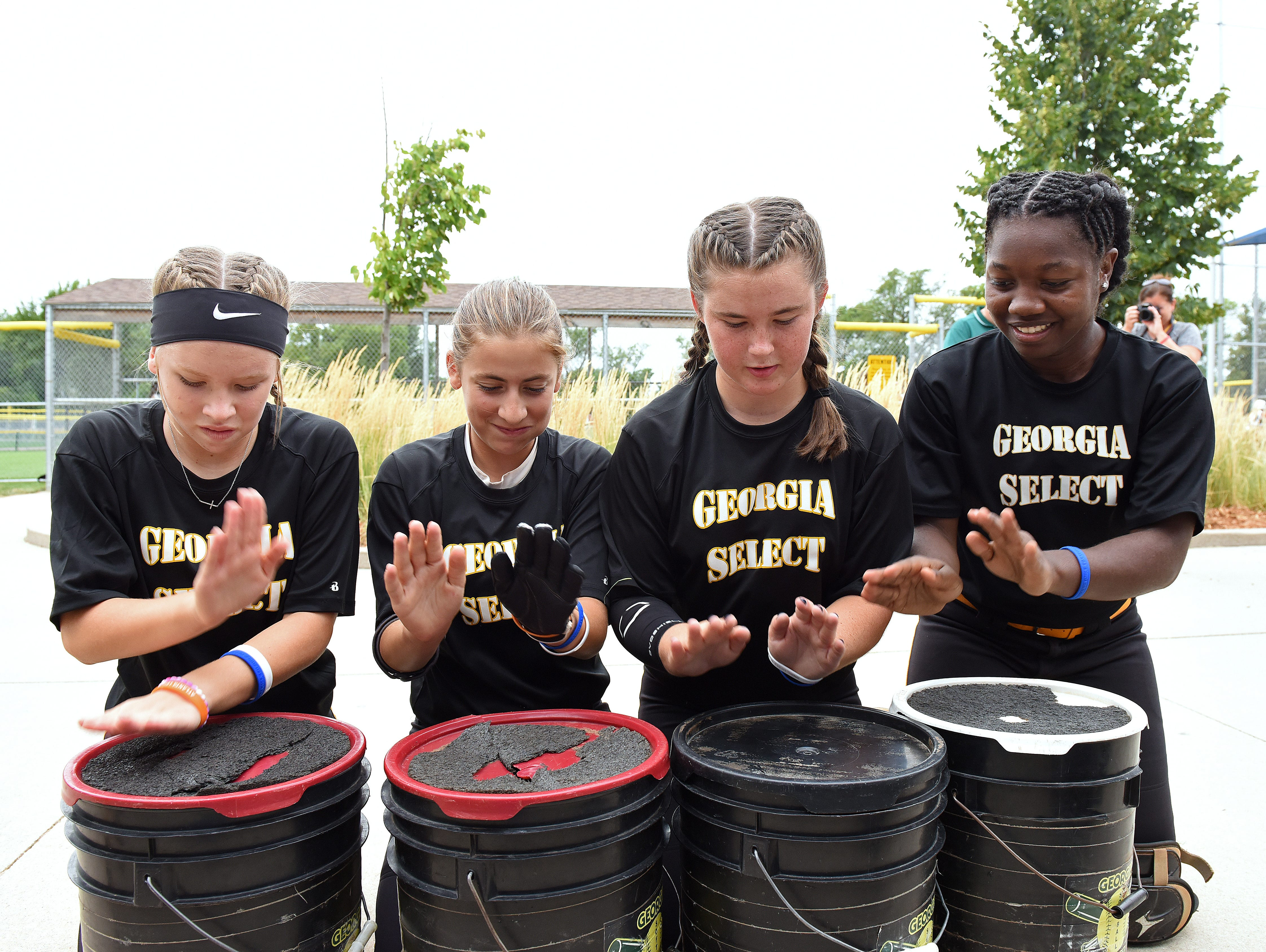 George Select's Skylar Berkhiser, Jenna Carpinello, Madyson Coe and Morgan Hall chant before they play during the ASA 14U national softball tournament at Sherman Park in Sioux Falls, S.D., Monday, Aug. 1, 2016.