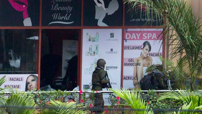 A Kenyan soldier prepares to enter the Westgate mall, following a bout of heavy gunfire with al-Qaeda-linked terrorists just after dawn Sept. 24 in Nairobi, Kenya.