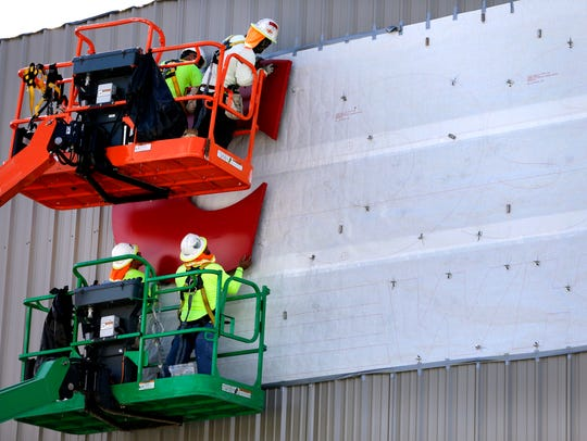 Construction workers raise a large C Monday while putting