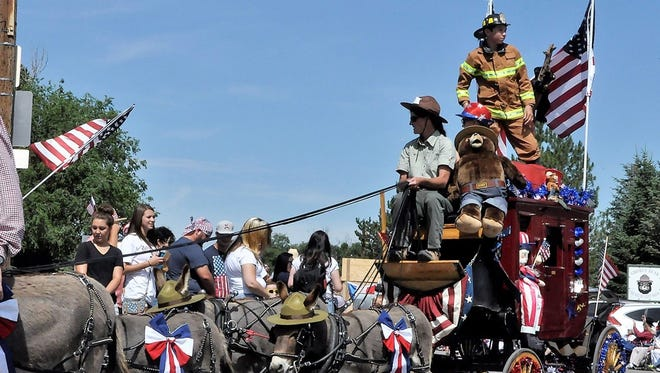 Some four-leffed firefighters pull a U.S. Forest Service float last year.