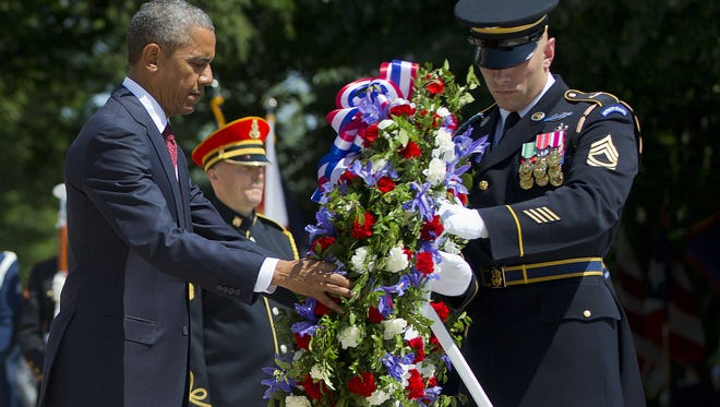 President Barack Obama and with the aid of Sgt. 1st Class John C. Wirth lays a wreath at the Tomb of the Unknowns, on Memorial Day, Monday, May 25, 2015, at Arlington National Cemetery.