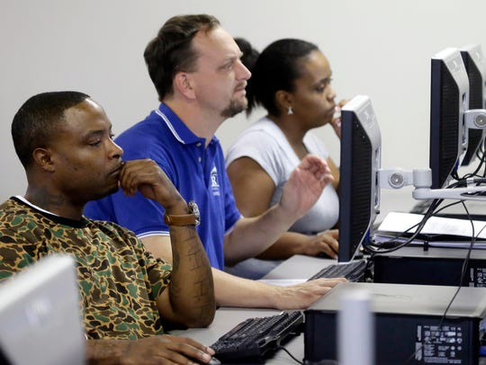 Job seekers look at their respective computer screens