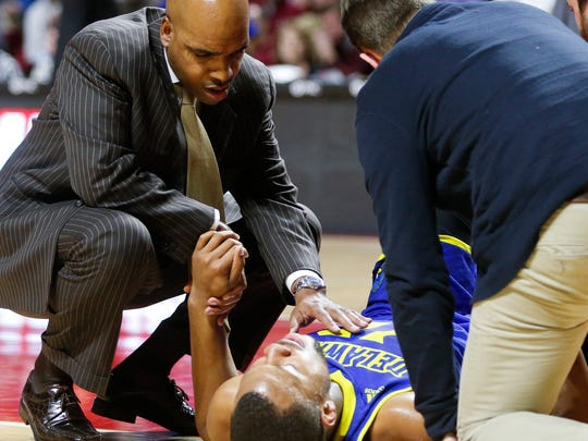 Delaware head coach Monte Ross visits with fallen Chivarsky Corbett, who tore his ACL late in the first half of a loss to Temple at the Liacouras Center in Philadelphia Sunday.