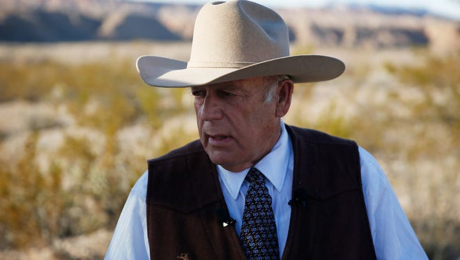 In this Jan. 27, 2016, file photo, rancher Cliven Bundy stands along the road near his ranch in Bunkerville, Nev.