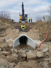 Workers repair a storm water main along Memorial Drive