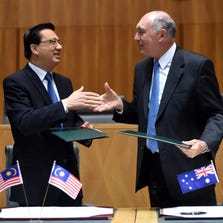 Australian Deputy Prime Minister Warren Truss, right, and Malaysian Transport Minister, Liow Tiong Lai shake hands after signing a Memorandum of Understanding at Parliament House in Canberra, Australia, Thursday.