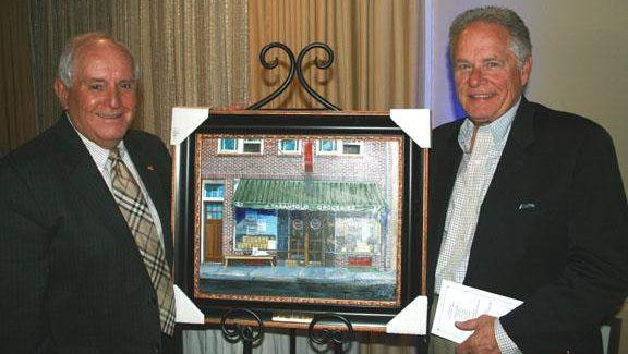 Former Eatontown Mayor Gerry Tarantolo (left) stands with artist Bob Stetz by the painting of the Tarantolo familys Long Branch grocery store and bakery, circa 1937.