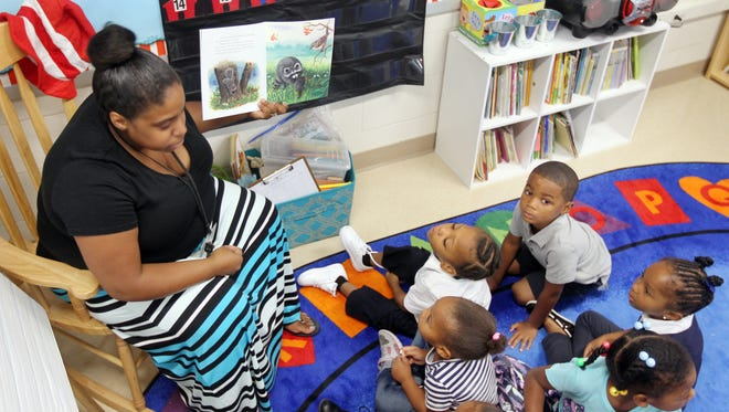 Rising Stars Academy teacher Becky Crabtree reads a book to students at the new school in the Over the Rhine. The school was opened in response to a partnership to expand preschool access in CPS and through community partners. Research shows an investment in quality preschool yields high educational returns, especially among children in economically disadvantaged families. ÊThe Enquirer/Patrick Reddy