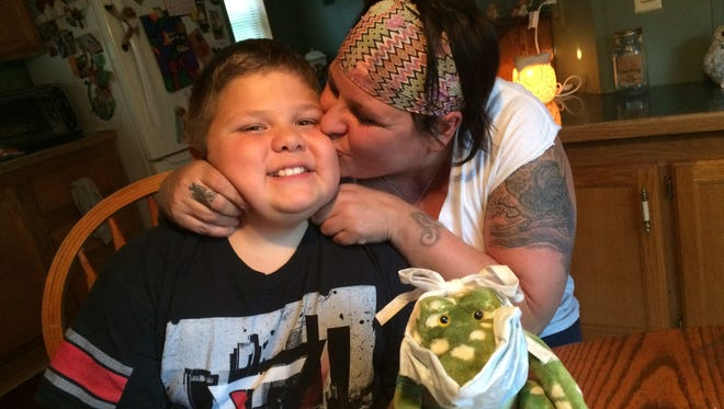 Jennifer Delikowski gives her son Trinton Cleveland a kiss at their home in rural Marathon County. A stuffed alligator sits on the table in front of them. It was used to help Trinton understand medical procedures when he was sick with cancer.