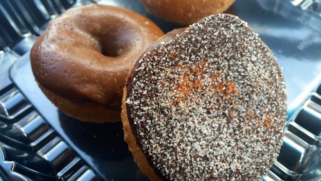 A Spicy Mexican Chocolate doughnut from Peace, Love & Little Donuts in Naples leans against a caramel doughnut with Himalayan salt.