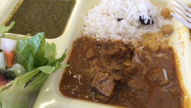 Lamb curry with basmati rice, chickpeas, spinach dhal, salad and raita, from Ahana's Bombay Grille in Bonita Springs.
