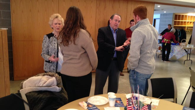 Republican presidential candidate Mike Huckabee talks with a supporter in Ames on Monday.