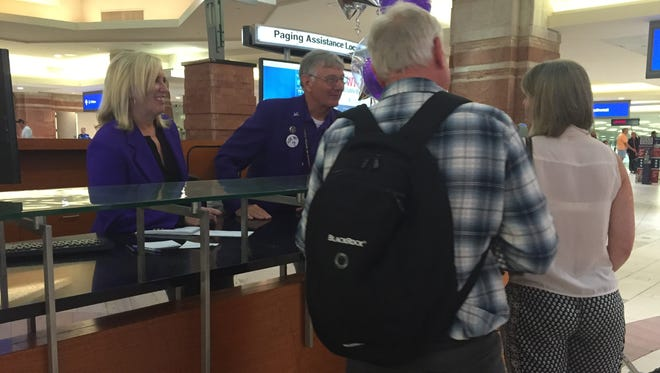 Tom Joy, a volunteer Navigator at Phoenix Sky Harbor International Airport, shows Republic reporter Dawn Gilbertson the ropes of helping travelers at the information desk in Terminal 4.