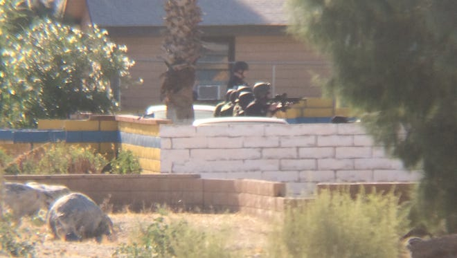 Officers pointing guns at a home near Desert View and Cactus Drive in Desert Hot Springs Thursday. They were trying to convince a suspect to surrender during a gang sweep that ended with 10 arrests.
