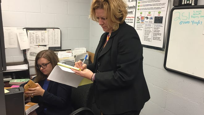 Assistant County Attorney Amelia Aslam, left, and Amy Hannah of the Louisville Metro Public Defender's Office literally work closely together at arraignment court in Louisville Metro Corrections as part of a new effort to expedite low-level cases.