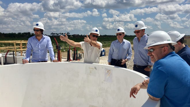 Johan Andreassen (second from left), the CEO of Atlantic Sapphire, shows a group of investors the first tanks that will be used to raise land-based salmon at the company's facility that is being built south of Miami, Fla., on April 9, 2018.