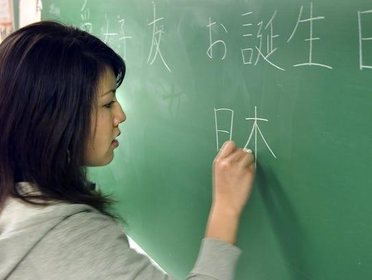 Hitomi Moriwaki, 17, writes out Japanese characters