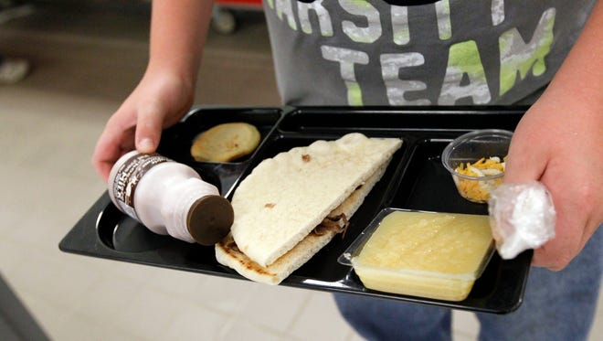 Last year, a student at Eastside Elementary School in Clinton, Miss., holds a lunch served under federal standards. It consisted of a flatbread roast beef sandwich, apple sauce, chocolate milk and a cookie. After just one year, some schools across the nation are dropping out of what was touted as a healthier federal lunch program.
