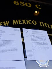 Official notices from the State of New Mexico can be seen taped to the door of New Mexico Title Company on Feb. 7, 2012, as state investigators audit the company.