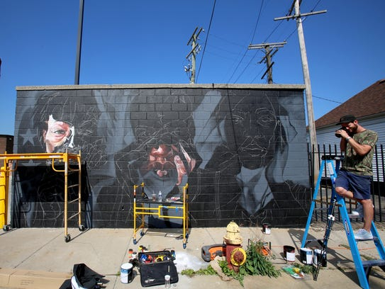 Elliot O'Donnell takes photo by the mural he and Sydney