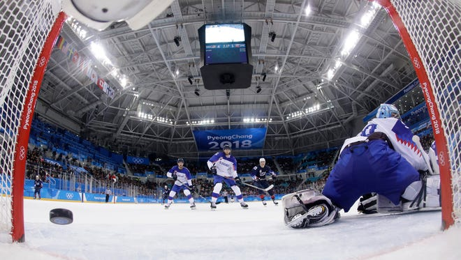 The puck shot by Ryan Donato of the United States sails past Jan Laco of Slovakia during their game Tuesday.
