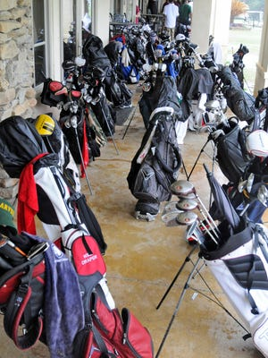 Golf bags under the back porch at Arrowhead Country Club after golfers returned from the course during the Greater Montgomery High School Golf Championship golf tournament on Monday, April 14, 2014.