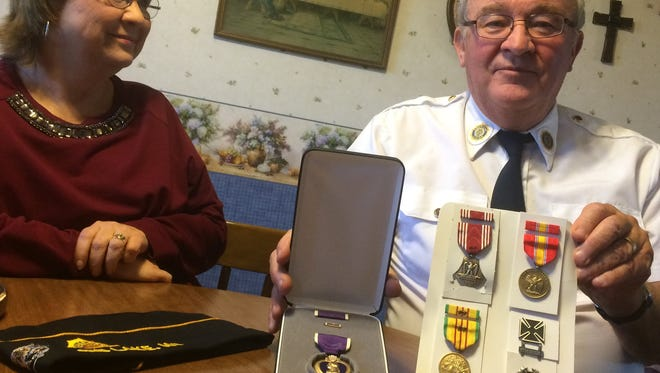 Jeff Zondlo, who was wounded in Vietnam on June 11, 1969, shows the Purple Heart and other medals he has received this year. He'll have the Purple Heart bestowed to him in a special ceremony in Rib Lake on Veterans Day. His wife, Candy Zondlo, looks on.