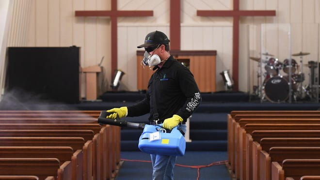 "Binmasters staffer Dustin Shock uses a spray gun to disinfect the sanctuary of Primera Iglesia Bautista Del Norte in Stockton in preparation for the first Sunday service in several months. The church will have restrictions in place, with services shortened to an hour, the Rev. Pablo Zelaya said. Binmasters, a local company started in August, does residential and Dumpster cleaning, Shock said, and is cleaning the worship centers near cost ""because people have to get back to worshipping."""