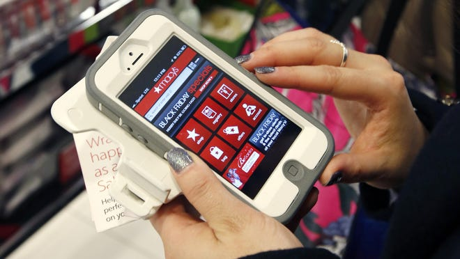 Tashalee Rodriguez uses a smartphone app while shopping at Macy's in downtown Boston in this 2012 file photo. For the first time, analysts predict more than half of online traffic to retailer sites will come from smartphones than desktops during the busy Black Friday holiday shopping weekend.