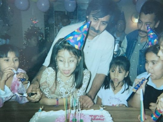 An old photo of Sydni Flores and her family celebrating a birthday in their home at the Tempe Mobile Home Park.