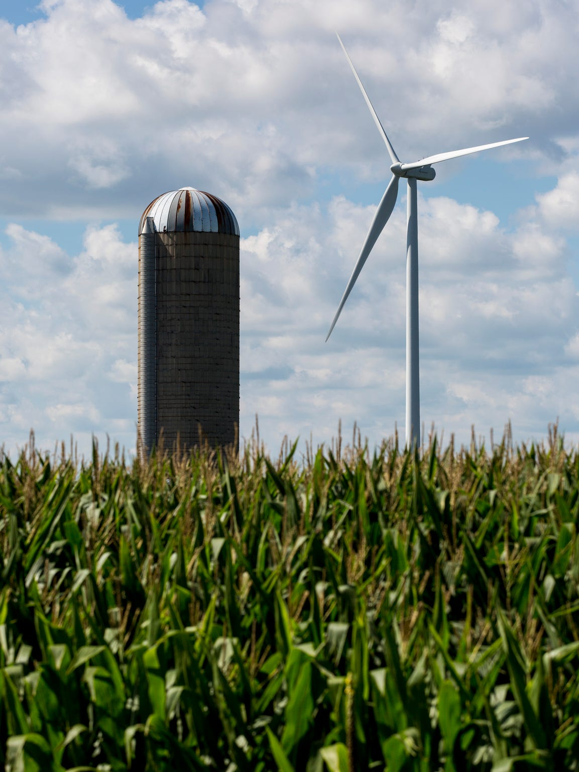 A wind turbine is seen beyond a silo Thursday, August 18, 2016 in Marion Township.