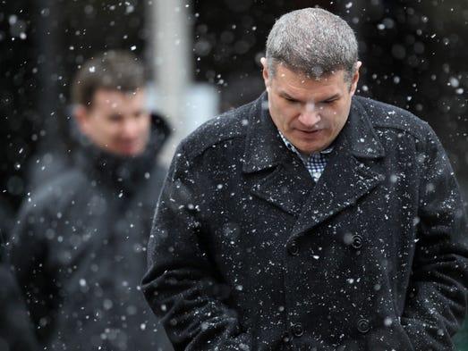 Pedestrians walk along South Elm Street during a snow shower in Greensboro, N.C.