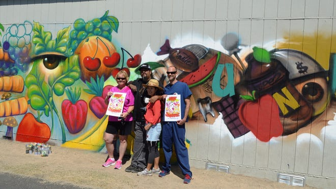 """Standing in front of a mural recently completed at Sunny Sands Elementary School in Cathedral City are (left to right) program coordinator Kelly Hughes, artists Vial Reyes and Erin Yoshi, and """"Dunk the Junk"""" founder and pediatrician Dr. Kevin Strong."""