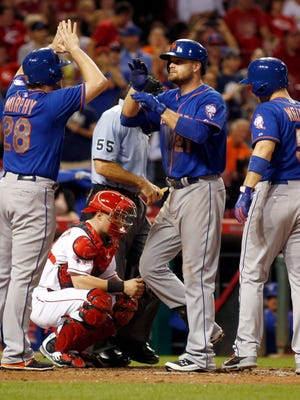 New York Mets first baseman Lucas Duda (21) is congratulated by second baseman Daniel Murphy (28) and third baseman David Wright (5) after Duda hit his second three-run home run of the game against the Cincinnati Reds in the seventh inning at Great American Ball Park.