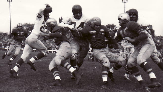 Defensive halfback Rebel Steiner (74) is in the middle of the scrum as Green Bay Packers' defense closes in on a Philadelphia ball carrier during a 37-24 victory over the Eagles at old City Stadium on Oct. 14, 1951. Other Packers defenders are, from left, Abner Wimberly (16) and Dick Wildung (45).