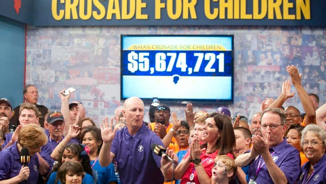 The Grand total of the 62nd WHAS Crusade for Children, announced by Terry Meiners, center, is $5,674,721.07 June 2015