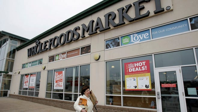 In this Thursday, March 27, 2014 photo, a woman walks out of the Whole Foods Market in Woodmere Village, Ohio. Whole Foods reports quarterly financial results on Wednesday, Nov. 5, 2014. (AP Photo/Tony Dejak) ORG XMIT: NYBZ144