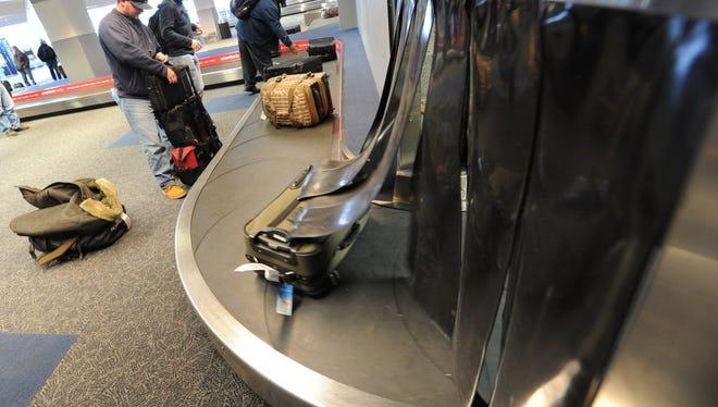 Passengers grab their luggage at Harrisburg International Airport on Friday, Jan. 30, 2015.