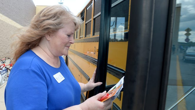 Communities in Schools Executive Director Becky Murray carries school supplies onto a school bus during a July 2016 Stuff the Bus with school supplies event at Wal-Mart.