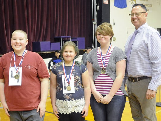 Lyon County's seventh-grade spelling champions (from left) Morgan Bumgardner, Heavyn Hill and Molly Gibbs pose for a photo with Principal Sean Moyle.