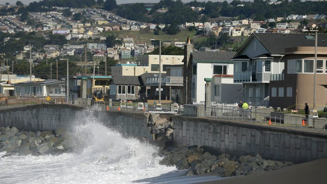 FILE - In this file photo from Monday, Jan. 25, 2016, waves crash near a damaged section of seawall in Pacifica, Calif.