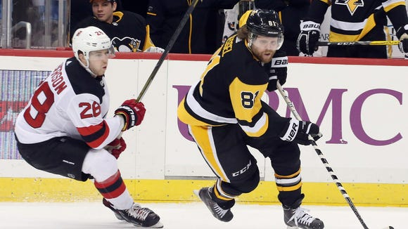 Pittsburgh Penguins right wing Phil Kessel (81) skates with the puck against New Jersey Devils defenseman Damon Severson (28) during the second period at PPG PAINTS Arena.