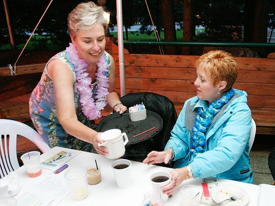 Howell Area Chamber of Commerce President Pat Convery serves coffee to Julie Burns in this file photo taken Saturday, Aug. 14, 2004 at the Livingston County Humane Society's Bow Wow and Meow Luau at Rocky's of Brighton.