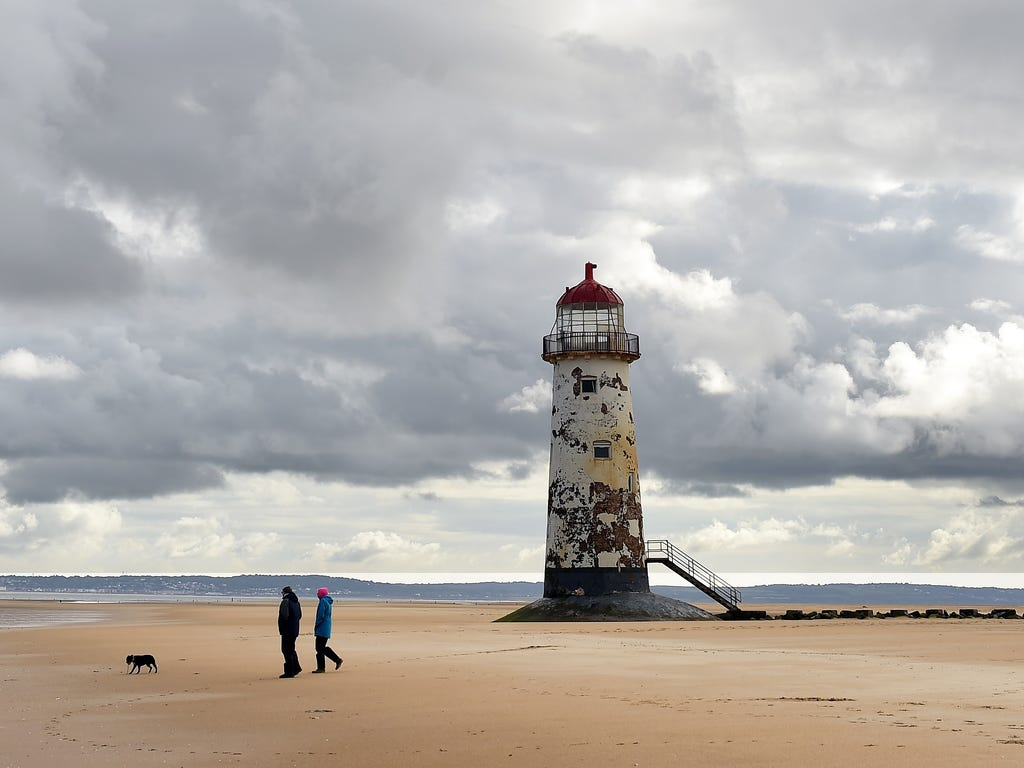 People walk as they cross the beach near the Point of Ayr Lighthouse in Talacre in north Wales.