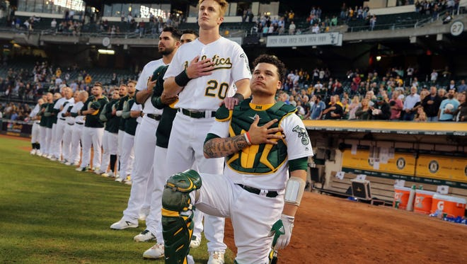 Athletics catcher Bruce Maxwell takes a knee during the national anthem before a game against Seattle on Sept. 25.
