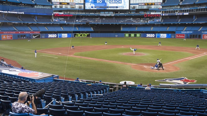 A photographer covers the game in an empty stadium during fourth-inning intrasquad baseball game action in Toronto, Friday, July 17.