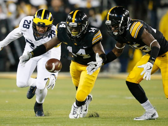 Iowa cornerback Desmond King bobbles the ball but is able to recover as he and Iowa cornerback Joshua Jackson (right) and Michigan's Brandon Watson go after the ball Saturday, Nov. 12, 2016, at Kinnick Stadium in Iowa City.