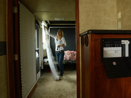 Baylee Hart hangs up her prom dress in a camper she will use to prepare for her senior prom after racing in the Muddin' at the Moose mud hop event on Saturday, April 11, 2015.
