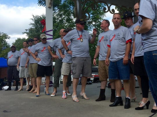 Twelve men, who work in law enforcement, strapped on high heels Saturday for the first annual Walk a Mile in Her Shoes event at Gypsy Hill Park.
