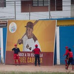 """Two boys stand in front of a fast food advertisement featuring hometown athlete, Detroit Tiger's Miguel Cabrera, during a baseball practice in Maracay, Venezuela on March 28. Cabrera's uncle seems unfazed by the news that the Detroit Tigers slugger has netted the richest contract in history of any U.S. sport. Like the rest of the neighborhood, he thinks """"Miguelito,"""" as many in his hometown still call him, was destined for greatness."""